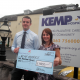Tesco manager Mike Burke hands over £1,000 to Kemp Hospice community fundraiser Sam Howell