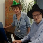Practicing the Twelve Days Christmas, Marguerite Clarke assists hospice patient, Mr Stanley Robinson, who has taken up playing the piano, a new hobby, whilst attending the Hospice.