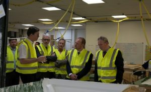 Chairman Mike Wheeler (left) gives members of the automotive supply chain a tour of Truckman's hardtop production facility.