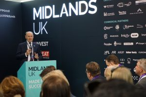 Sir John Peace speaking at an event inside the Midlands UK Pavillion